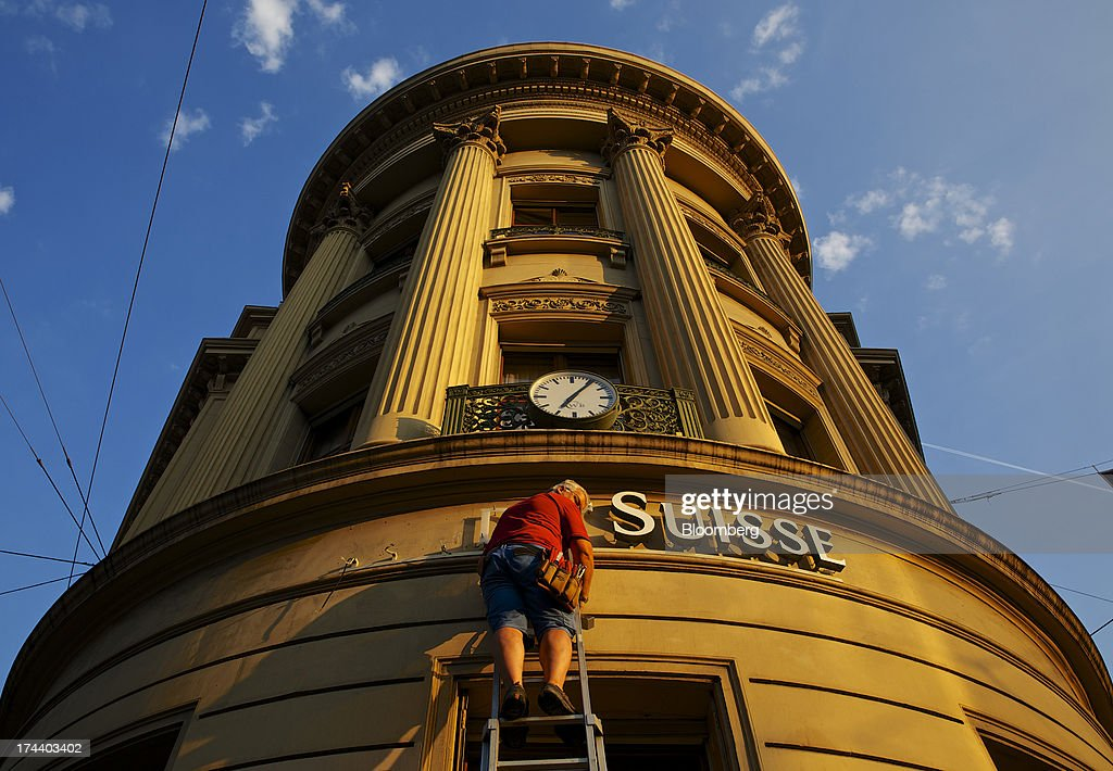A worker stands on a ladder as he replaces letters of the company's sign on the offices of Credit Suisse Group AG in Basel, Switzerland, on Tuesday, July 23, 2013. Europe's biggest banks, which more than doubled their highest-quality capital to $1 trillion since 2007 to meet tougher rules, may have further to go as regulators scrutinize how lenders judge the riskiness of their assets. Photographer: Gianluca Colla/Bloomberg via Getty Images