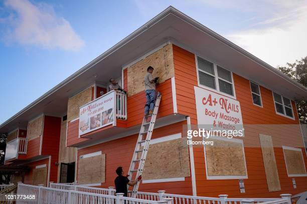 A worker stands on a ladder while securing plywood to windows ahead of Hurricane Florence in Carolina Beach North Carolina US on Tuesday Sept 11 2018...