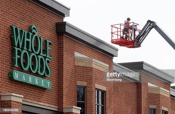 Worker stands on a lift at the entrance of a new Whole Foods Market Inc. Store under construction in Park Ridge, Illinois, U.S., on Tuesday, Sept....