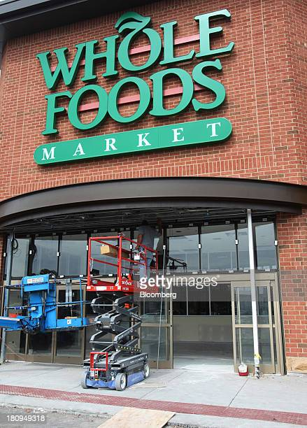 Worker stands on a lift under the awning outside a new Whole Foods Market Inc. Store under construction in Park Ridge, Illinois, U.S., on Tuesday,...