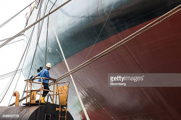 A worker stands on a platform next to the Tullow Oil Plc Prof John Evans Atta Mills Floating Production Storage and Offloading vessel at the Sembcorp...