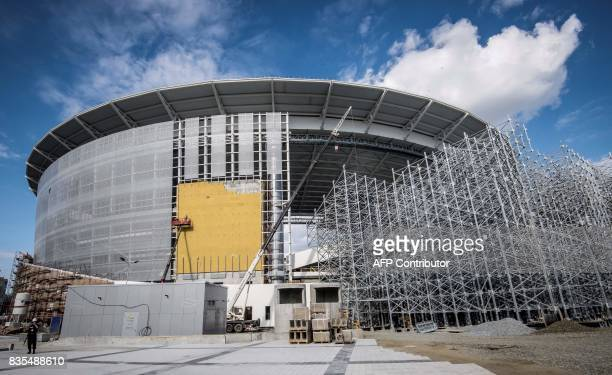 A worker stands on August 19 2017 in front of the Yekaterinburg Arena under renovation work in Yekaterinburg The Yekaterinburg Arena will host...