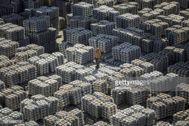 A worker stands on bundles of aluminum ingots at a China National Materials Storage and Transportation Corp stockyard in Wuxi China on Thursday Aug...