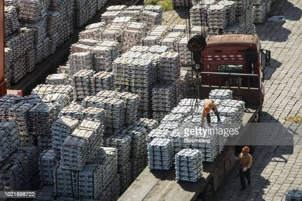 A worker stands on bundles of aluminum ingots on the back of a truck at a China National Materials Storage and Transportation Corp stockyard in Wuxi...