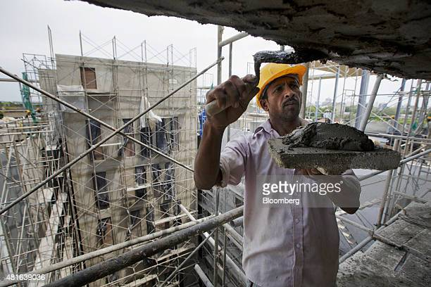 A worker stands on scaffolding as he trowells cement at the construction site of the 7thSense apartment project condominium project developed by John...