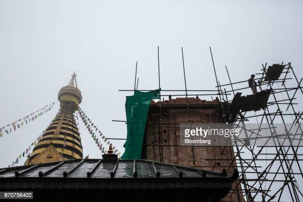 A worker stands on scaffolding at a construction site next to the Swayambhunath Stupa in Kathmandu Nepal on Wednesday Nov 1 2017 India and China have...