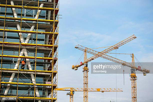 Worker stands on scaffolding surrounding the 50Hertz Transmission GmbH headquarter, with construction cranes in the distance, as it is built on the...