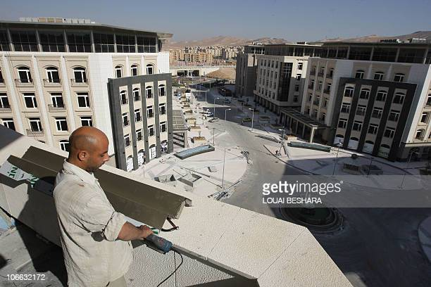 HADDAD A worker stands on the balcony of housing blocks constructed by the Dubai Emaar company in conjunction with the Syrian Overseas Investment...