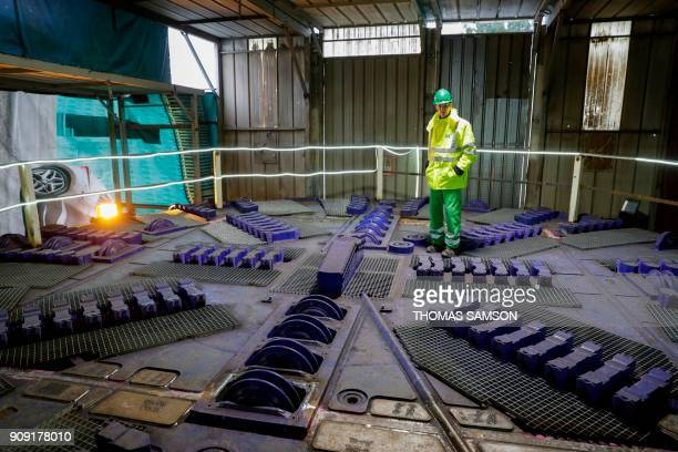 A worker stands on the head of the tunnel boring machine not yet assembled at the drilling site of the future Metro Line 15 South of the Grand Paris...