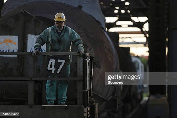 A worker stands on the rear platform of a bottle car full of molten steel inside the ArcelorMittal steel mill complex in Cleveland Ohio US on Friday...