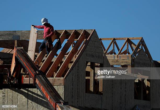 A worker stands on the roof of a home under construction at a new housing development on November 17 2016 in San Rafael California According to a...