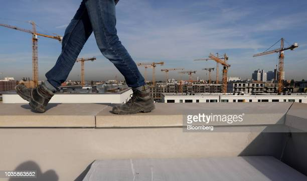 A worker stands on the upper level of a semi complete property construction at the Europacity urban development project building site in Berlin...
