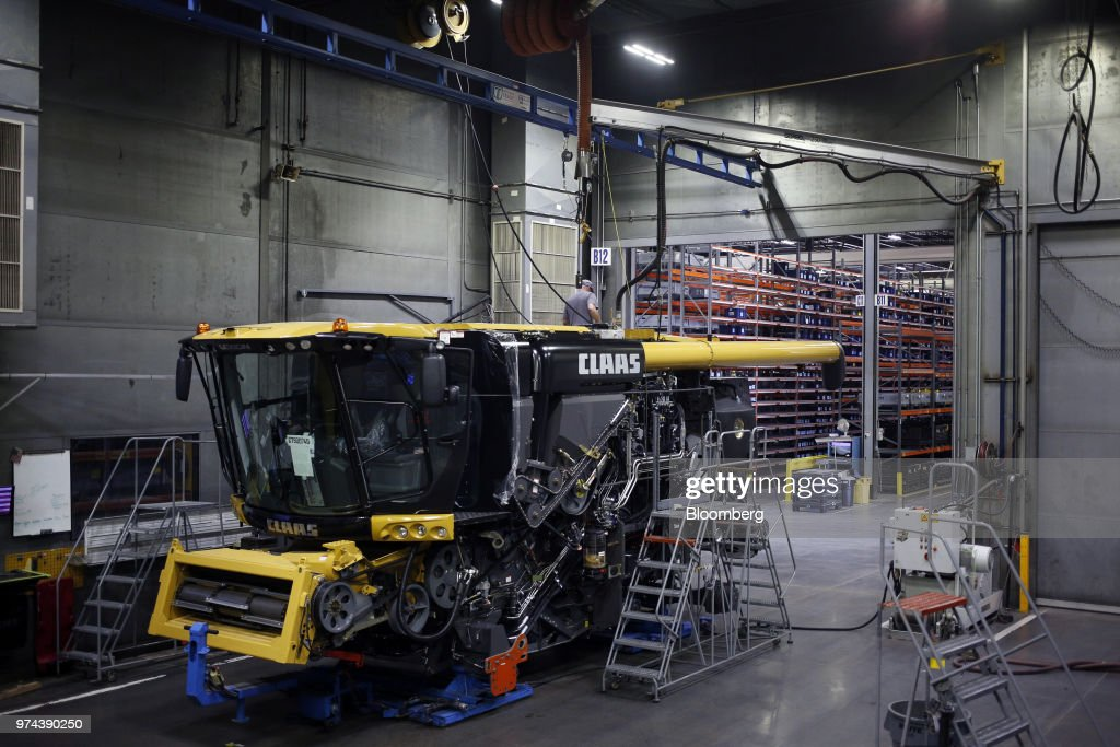 A worker stands on top of a combine harvester on the assembly line at the CLAAS of America Inc. production facility in Omaha, Nebraska, U.S., on Wednesday, June 6, 2018. The Federal Reserve is scheduled to release industrial production figures on June 15. Photographer: Luke Sharrett/Bloomberg via Getty Images
