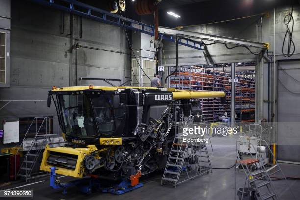 A worker stands on top of a combine harvester on the assembly line at the CLAAS of America Inc production facility in Omaha Nebraska US on Wednesday...