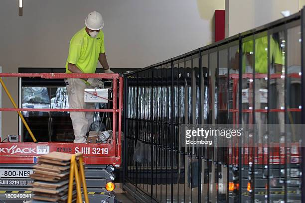 Worker stands over refrigerators inside a new Whole Foods Market Inc. Store under construction in Park Ridge, Illinois, U.S., on Tuesday, Sept. 17,...