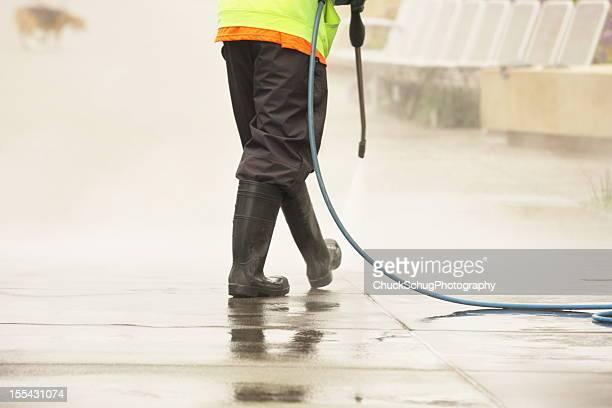 Worker Steam Cleans Sidewalk Dog