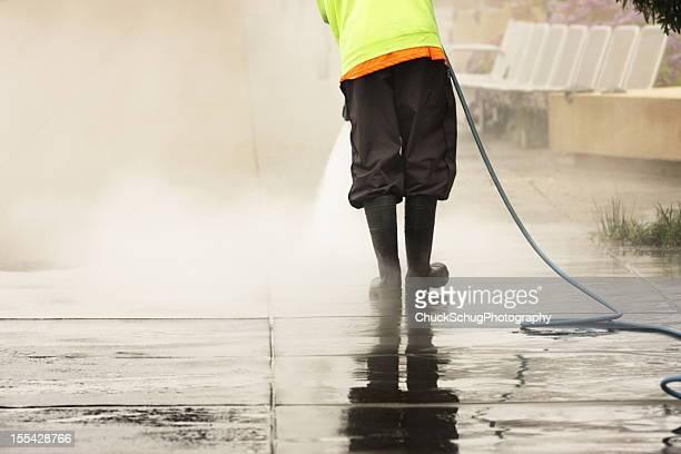 Worker Steam Cleans Sidewalk
