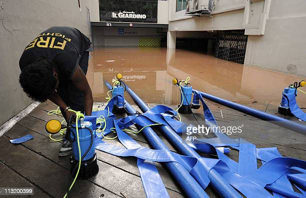 A worker stes up pumps to take away water from a basement carpark after flooding occured in low lying areas after heavy rain in Singapore on July 18...