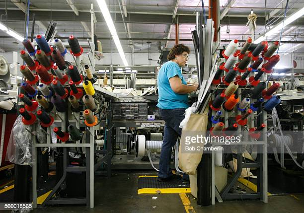 Worker stiches together leather seat covers with 200 parts at Katzkin Leather which produces leather goods used in making upholstery for upgrading...