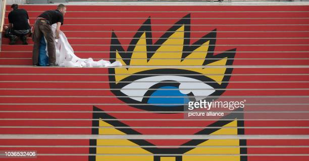 Worker sticks the logo of the Leipzig Book Fair to a flight of stairs at the glass hall of the Leipzig Trade Fair in Leipzig, Germany, 14 March 2017....