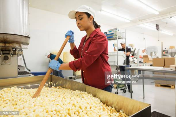 Worker stirring popcorn in factory