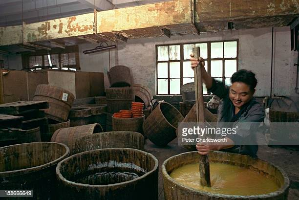 Worker stirs a huge tub of dye used for printing on silk at the Shanghai Number 7 Silk and Dyeing Factory..
