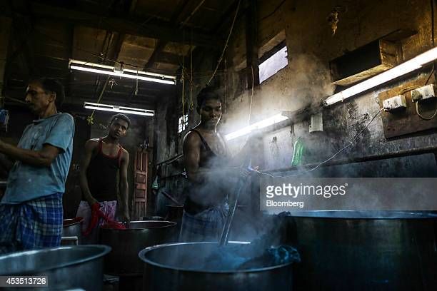 A worker stirs the contents of a metal vat while dyeing fabric in a workshop in the Dharavi slum area of Mumbai India on Monday Aug 11 2014 Almost a...