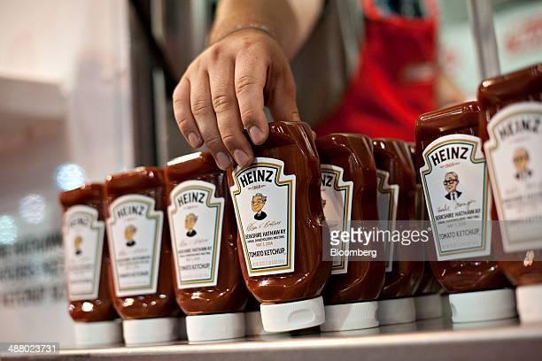 A worker stocks bottles of Heinz ketchup bearing a caricature of Warren Buffett chairman of Berkshire Hathaway during the Berkshire Hathaway...