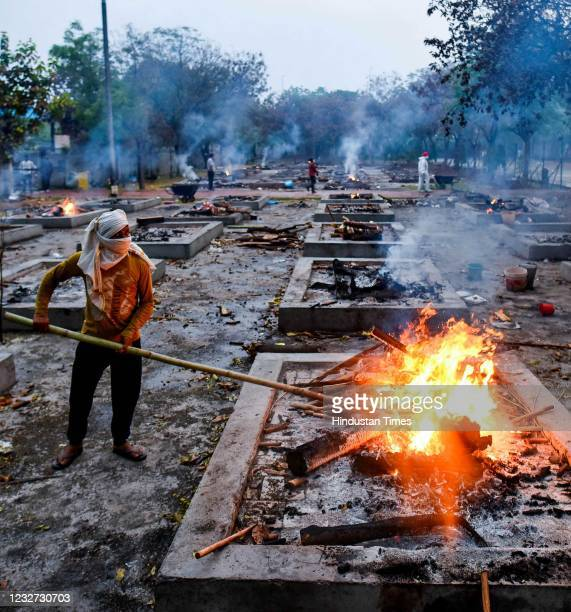 Worker stokes a funeral pyre during cremations of Covid-19 victims at Sarai Kale Khan crematorium on May 6, 2021 in New Delhi, India.