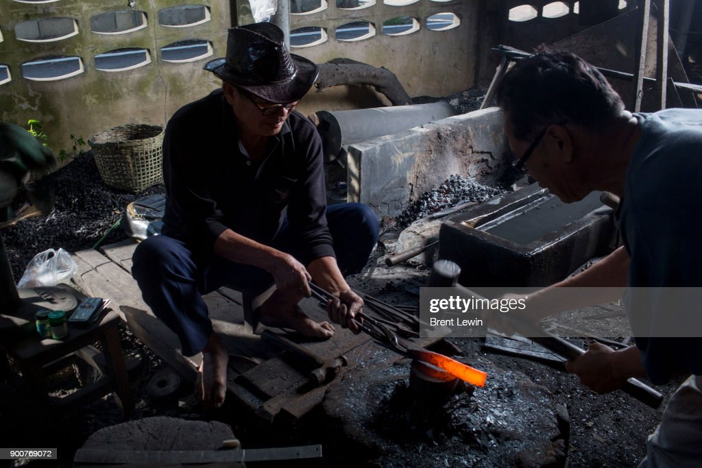 A worker strikes a heated piece of steel at a workshop on December 19, 2017 in Lampang, Thailand. The craft of sword making is dying in Thailand and Boontan Sittipaisal is one of the country's remaining people who are still making the dah, a Burmese word that means 'blade', which represents a long history of sword making across Indochina. The single-edged sword stretches out from a round handle with a subtle curve that widens toward the tip and was used in Thailand during the Ayutthaya period as weapons but later incorporated into ceremonial dances, physical education classes, and martial arts. Boontan, his brother Boonsoung, and a team of craftsmen finish about ten swords each day at their workshop located at the suburb of Hang Chat in Lampang, forging the swords by hand while paying attention to quality and passing on the endangered art to the next generation in hopes that it will not die.