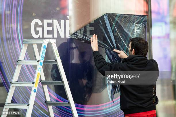 Worker strips down the banners due the cancellation of the Geneva Auto Show on February 28, 2020 in Geneva, Switzerland. Swiss authorities announced...