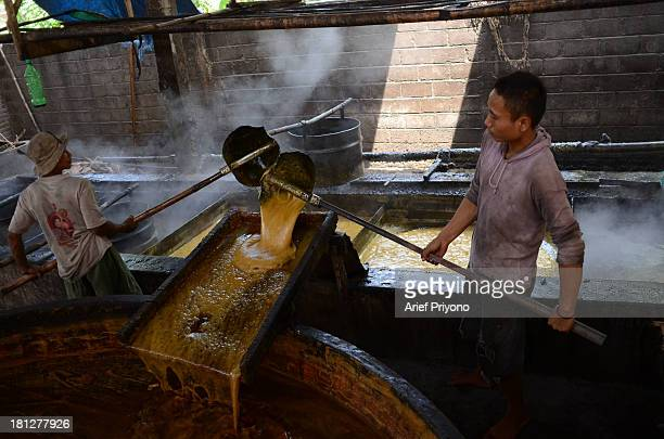 A worker supervising boiling vats of sugar cane juice while making brown sugar in a small factory in Slumbung village Most Indonesian people use...