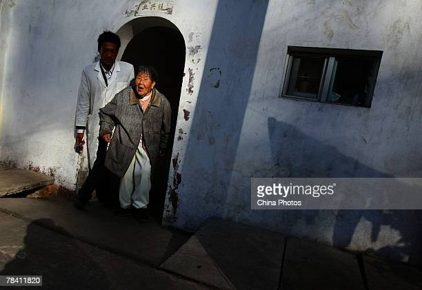 A worker supports a senior female resident at the Happy Times Nursing Home on December 12 2007 in Kunming of Yunnan Province China Twothirds of the...