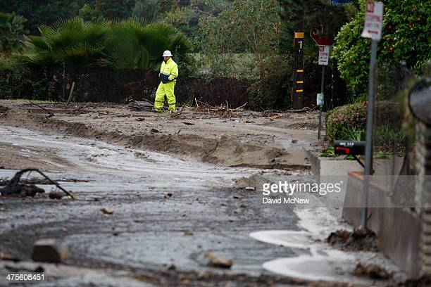 A worker surveys a debrisfilled street below the Colby Fire burn area as a storm brings rain in the midst of record drought on February 28 2014 in...