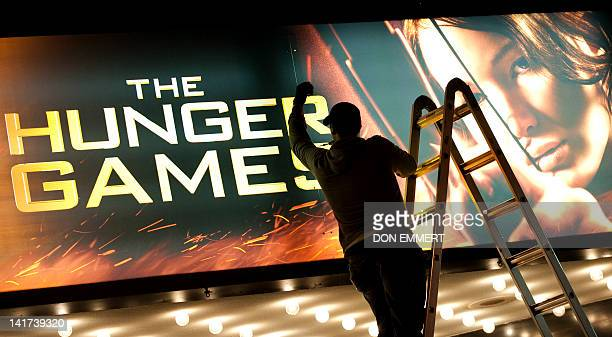 A worker swaps out the billboard marking the opening of 'The Hunger Games March 22 2012 at the Ziegfeld Theatre in New York The science fiction...