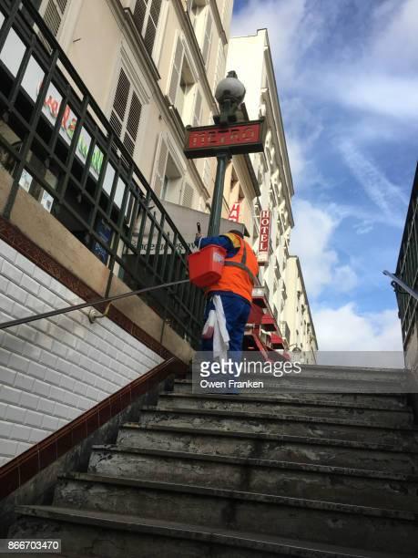 worker sweeping stairs of the metro at Place de la Republique-Paris