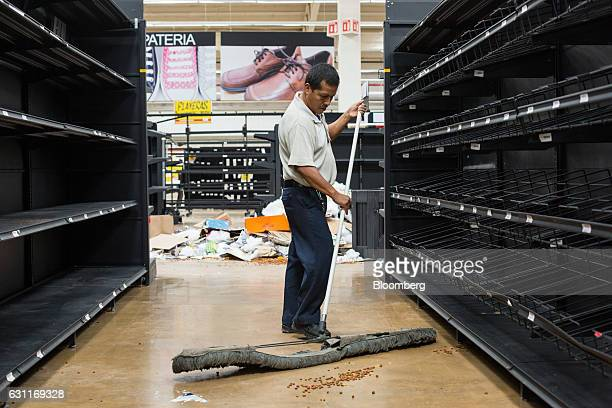 A worker sweeps debris inside a Grupo Comercial Chedraui SA store after looting in Veracruz City Mexico on Saturday Jan 7 2017 Mexico's National...