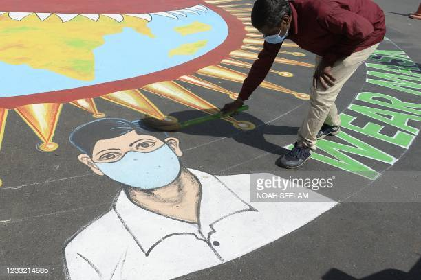 Worker sweeps dust on a graffiti depicting Covid-19 coronavirus safety protocols during an awareness campaign at a traffic junction in Hyderabad on...