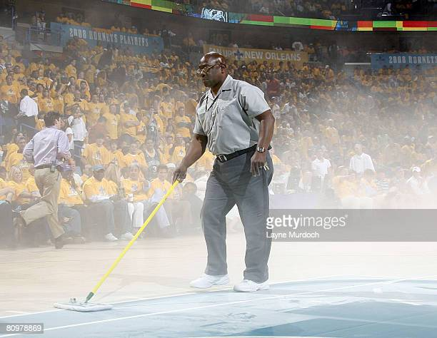 A worker sweeps fire extinguisher dust from the court during Game One of the Western Conference Semifinals during the 2008 NBA Playoffs at New...
