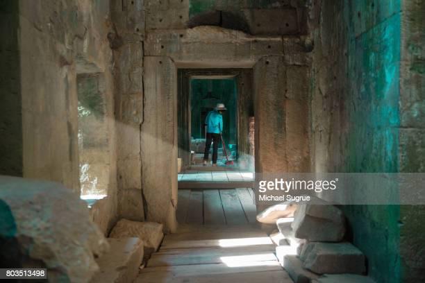 a worker sweeps inside ta prohm temple, near angkor wat, siem reap, cambodia. - archäologie stock-fotos und bilder