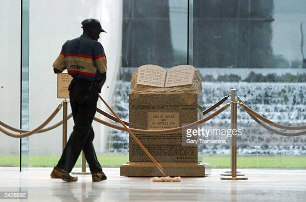 A worker sweeps near the Ten Commandments monument in the rotunda of the state judicial building August 25 2003 in Montgomery Alabama Suspended...
