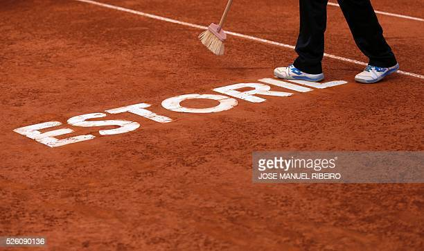 Worker sweeps the clay on the pitch of the central court of the Estoril Open Tennis tournament in Estoril on April 29, 2016. / AFP / JOSE MANUEL...