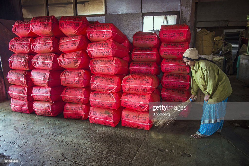 A worker sweeps the floor beside stacked bags of tea at the Santosh Tea Industries Pvt. factory in Coonoor, Tamil Nadu, India, on Saturday, Nov. 30, 2013. India is the worlds largest producer of tea after China. Photographer: Prashanth Vishwanathan/Bloomberg via Getty Images