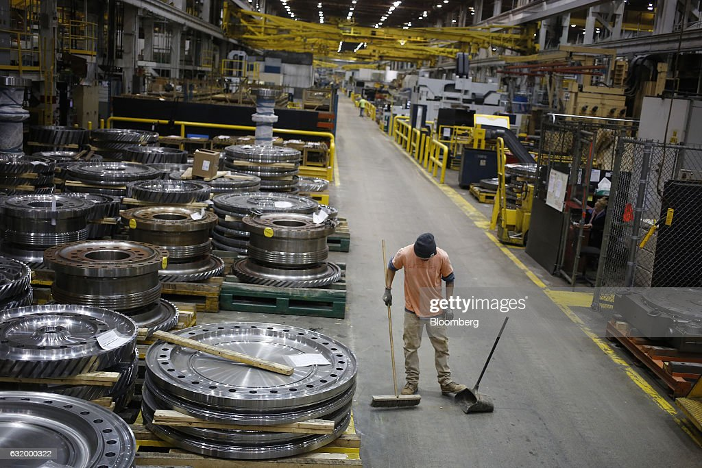 A worker sweeps the floor near gas turbine parts at the General
