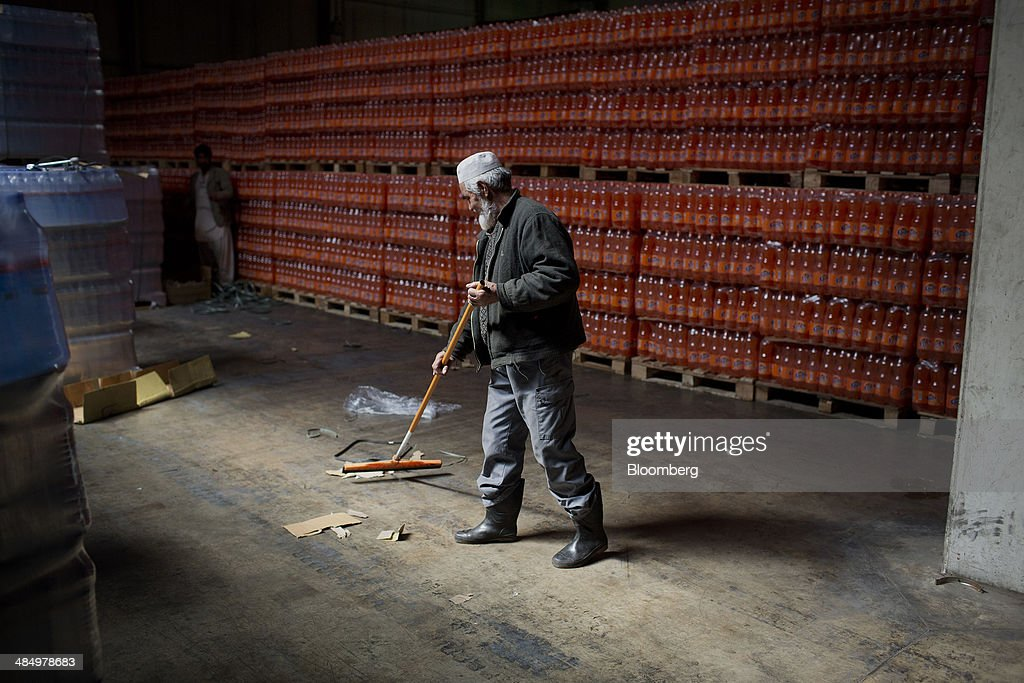 A worker sweeps the floor of a warehouse at the Habib Gulzar Non-Alcoholic Beverage Ltd. bottling facility in Kabul, Afghanistan, on Thursday, April 10, 2014. Coca-Cola Co., the world's largest soda maker, today showed signs of a rebound in the first three months of the year, easing the concerns that arose when the company unsettled investors with surprisingly sluggish global sales in the fourth quarter. Photographer: Victor J. Blue/Bloomberg via Getty Images