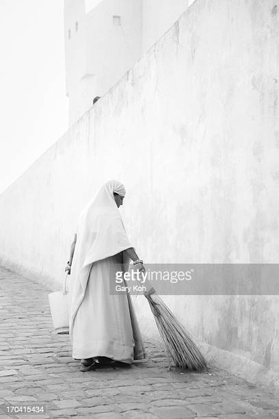 Worker sweeps the ground of the large walkway leading up to Ajmer Fort in India. Named after Amba, the Mother Goddess, Ajmer Fort is a majestic 16th...