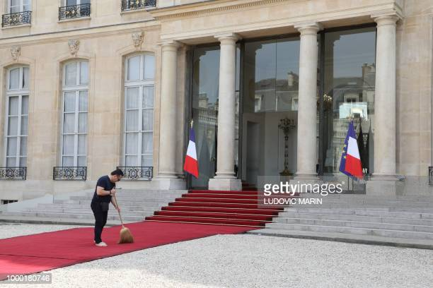 A worker sweeps the red carpet outside the Elysee palace on July 16 in Paris prior to the arrival of the French national football team for a meeting...