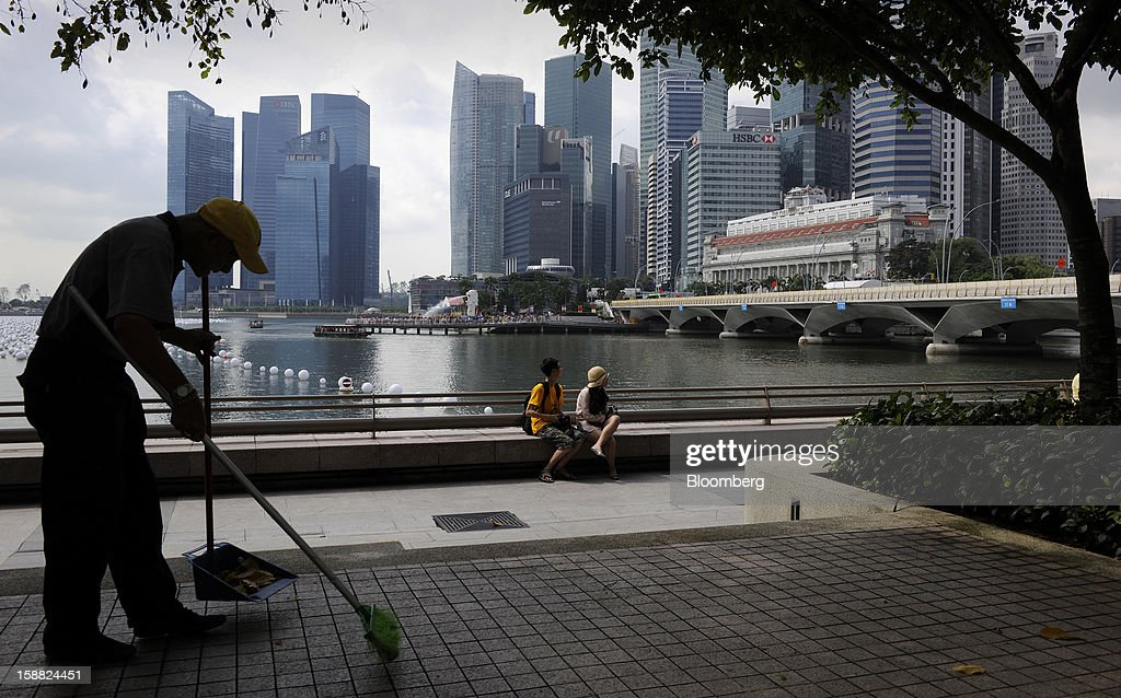 A worker sweeps up leaves on the waterfront across from the central business district in Singapore, on Sunday, Dec. 30, 2012. Singapore may grapple with elevated inflationary pressures for a third year in 2013, reducing scope for the central bank to provide stimulus to an economy that probably entered a technical recession this quarter. Photographer: Munshi Ahmed/Bloomberg via Getty Images