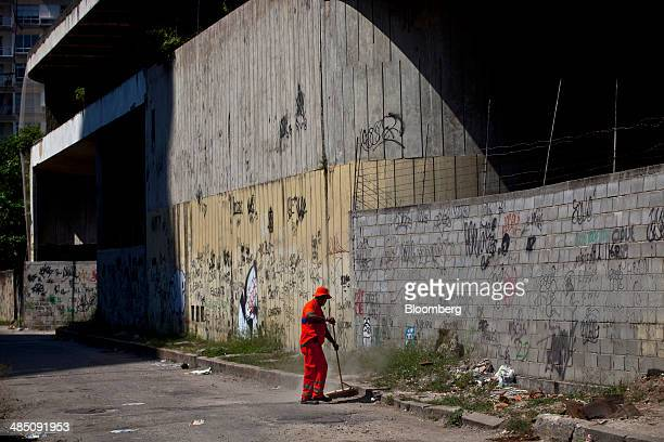 A worker sweeps up trash on the street next to the abandoned Hotel Nacional designed by architect Oscar Niemeyer in Rio de Janeiro Brazil on...