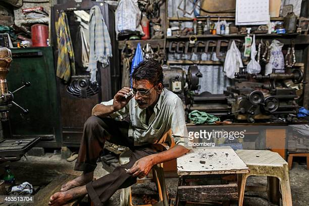 A worker takes a break at a metal workshop in the Dharavi slum area of Mumbai India on Monday Aug 11 2014 Almost a year after Reserve Bank of India...